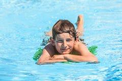Muchacho adolescente en la piscina que se relaja Fotografía de archivo libre de regalías