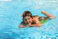 Muchacho adolescente en la piscina que se relaja Fotos de archivo