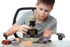 Muchacho adolescente en laboratorio de la escuela Investigador que trabaja con el microscopio Imágenes de archivo libres de regalías