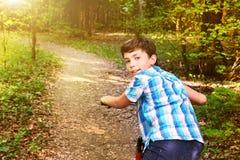 Muchacho adolescente en paseo de la bicicleta a través del bosque del verano Fotografía de archivo
