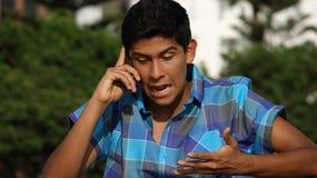 Muchacho adolescente enojado que habla en el teléfono celular Fotografía de archivo
