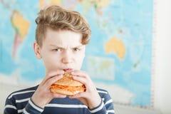 Muchacho adolescente enojado que intenta comer una hamburguesa de la zanahoria Fotografía de archivo libre de regalías