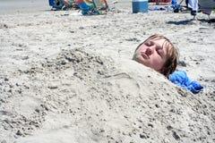Muchacho adolescente enterrado en arena Foto de archivo