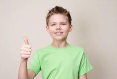 Muchacho adolescente feliz con el apoyo dental desprendible que muestra el pulgar encima de la más gest Imagenes de archivo