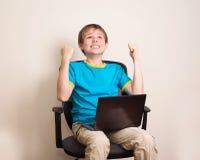 Muchacho adolescente feliz con el ordenador portátil en actitud que gana Niño del éxito en offic Fotos de archivo libres de regalías