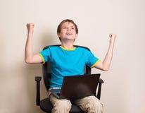 Muchacho adolescente feliz con el ordenador portátil en actitud que gana Niño del éxito en offic Fotografía de archivo