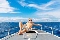 Muchacho adolescente feliz en gafas de sol en el yate Mar tropical en el b Foto de archivo libre de regalías