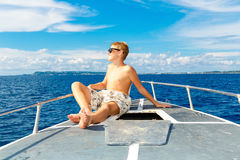 Muchacho adolescente feliz en gafas de sol en el yate Mar tropical en el b Foto de archivo