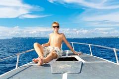 Muchacho adolescente feliz en gafas de sol en el yate Mar tropical en el b Fotos de archivo libres de regalías