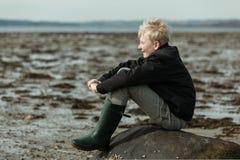 Muchacho adolescente feliz en las botas que esperan la marea Foto de archivo libre de regalías