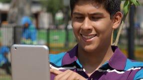 Muchacho adolescente feliz que usa la tableta Imagen de archivo