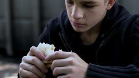 Muchacho adolescente hambriento que come el bocadillo malsano barato, comida de la mal calidad para el niño imagen de archivo
