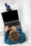 Muchacho adolescente hermoso con el ordenador portátil Fotos de archivo libres de regalías
