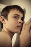 Muchacho adolescente joven con el oído presionado emparedar Fotos de archivo
