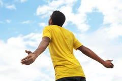 Muchacho adolescente joven con las manos abiertas al cielo Fotos de archivo