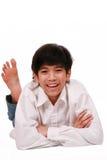 Muchacho adolescente joven hermoso que miente en suelo Imagen de archivo