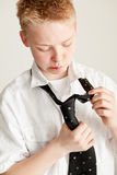 Muchacho adolescente joven que lucha con atar la corbata Imagenes de archivo