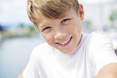 Muchacho adolescente joven que se coloca en la playa Imágenes de archivo libres de regalías