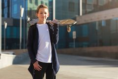Muchacho adolescente lindo con el monopatín al aire libre, colocándose en la calle foto de archivo libre de regalías