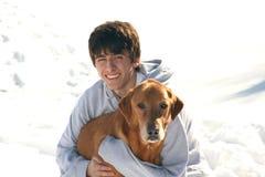 Muchacho adolescente lindo con el perro en la nieve Fotos de archivo