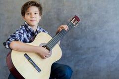 Muchacho adolescente lindo con la guitarra Imágenes de archivo libres de regalías