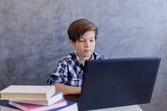 Muchacho adolescente lindo de la edad que trabaja en el ordenador portátil en casa Fotos de archivo libres de regalías