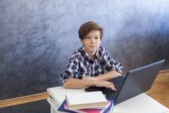 Muchacho adolescente lindo de la edad que trabaja en el ordenador portátil en casa Imagen de archivo