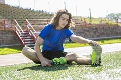 Muchacho adolescente listo para correr afuera en un campo de entrenamiento Imagen de archivo