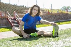 Muchacho adolescente listo para correr afuera en un campo de entrenamiento Fotografía de archivo libre de regalías