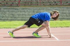 Muchacho adolescente listo para correr afuera en un campo de entrenamiento Imagenes de archivo