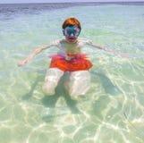 Muchacho adolescente pelirrojo con las gafas del salto que nada en el océano Imagen de archivo