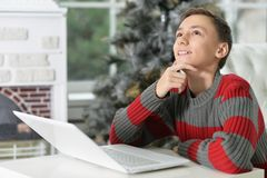 Muchacho adolescente pensativo con el ordenador portátil Fotografía de archivo libre de regalías