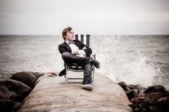 Muchacho adolescente pensativo que se relaja en la costa Imagen de archivo libre de regalías