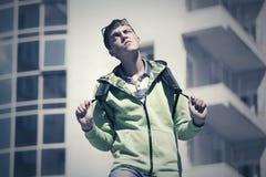 Muchacho adolescente que camina contra una construcción de escuelas Fotografía de archivo libre de regalías