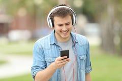 Muchacho adolescente que camina y que escucha en la línea música Fotografía de archivo libre de regalías