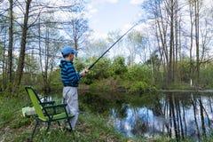 Muchacho adolescente que coge un pescado con la caña de pescar en la playa del lago Fotos de archivo