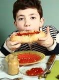 Muchacho adolescente que come el perrito caliente Fotografía de archivo libre de regalías