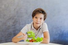 Muchacho adolescente que come la ensalada Imagen de archivo