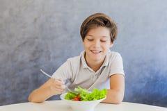 Muchacho adolescente que come la ensalada Foto de archivo libre de regalías