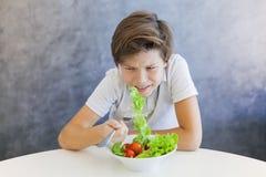 Muchacho adolescente que come la ensalada infeliz Imagen de archivo libre de regalías