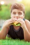 Muchacho adolescente que come la hamburguesa Imagen de archivo libre de regalías