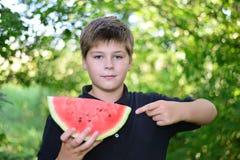 Muchacho adolescente que come la sandía en naturaleza Imagen de archivo libre de regalías