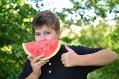 Muchacho adolescente que come la sandía en naturaleza Fotografía de archivo libre de regalías