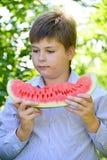 Muchacho adolescente que come la sandía en naturaleza Fotografía de archivo