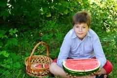 Muchacho adolescente que come la sandía en naturaleza Imagenes de archivo