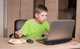 Muchacho adolescente que come las patatas fritas y que practica surf en Internet o playin Fotografía de archivo libre de regalías