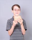 Muchacho adolescente que come un emparedado Imagenes de archivo