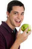 Muchacho adolescente que come una manzana Fotos de archivo
