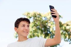 Muchacho adolescente que consigue una foto con el teléfono Fotos de archivo