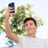 Muchacho adolescente que consigue una foto con el teléfono Foto de archivo